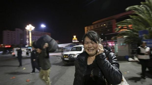 A woman reacts, at the crime scene outside a railway station after an attack, in Kunming, in southwestern China's Yunnan ...