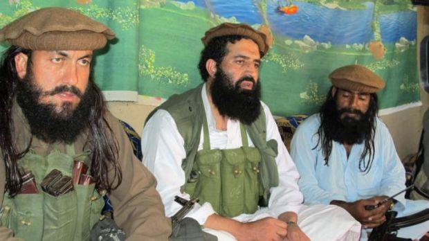 Shahidullah Shahid, centre, flanked by his bodyguards, talks to reporters at an undisclosed location in Pakistani tribal ...