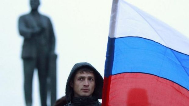 A man holds the Russian flag in front of a statue of Lenin in Simferopol, Crimea.