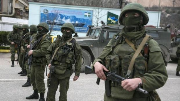 Occupation: Armed servicemen stand near Russian army vehicles in Crimea.