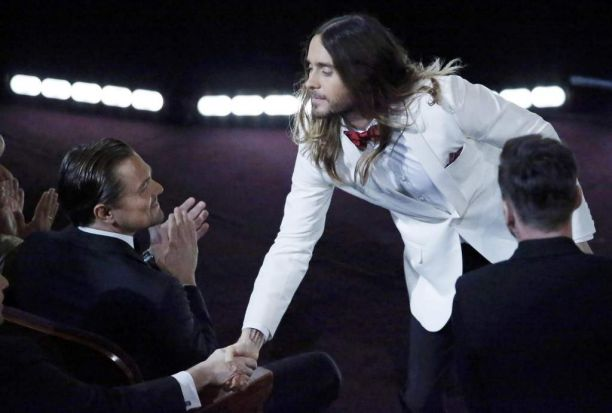 Jared Leto, best supporting actor winner, shakes hands with other nominee as Leonardo DiCaprio watches on.