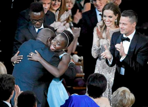 Lupita Nyong'o, best supporting actress winner for her role in <i>12 years a Slave</i>, hugs the movie's director Steve ...