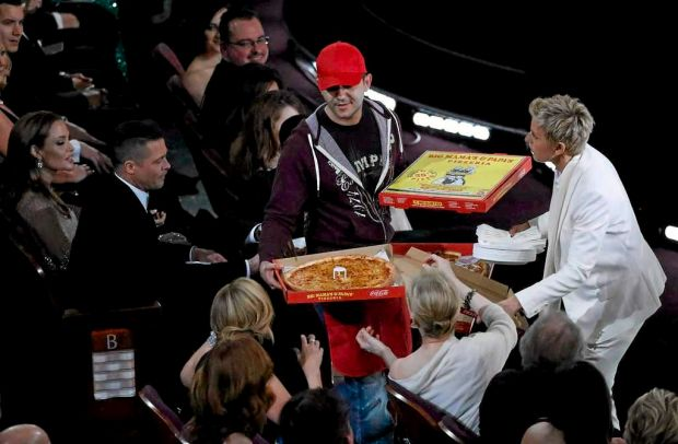 Show host Ellen DeGeneres (R) delivers pizza to the audience as actors Brad Pitt and Angelina Jolie (L) look on.