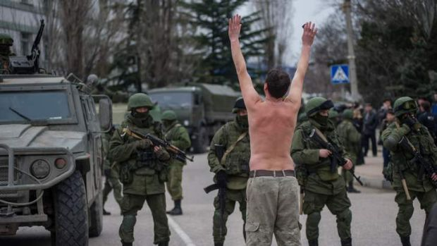A Ukrainian man stands in protest in front of gunmen in unmarked uniforms as they stand guard in Balaklava, on the ...