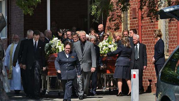 Mourners outside the church as caskets leave the funeral of Robert and Cheryl Adamson.