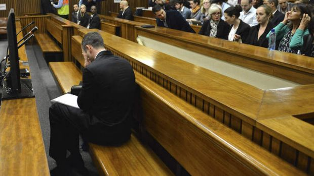 Bowing his head: Oscar Pistorius in the dock on the second day of his trial in Pretoria on Tuesday.