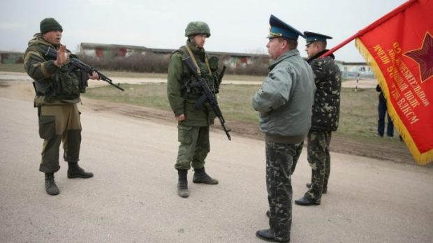 Tense exchange: Ukrainian soldiers, one bearing the regimental flag, confront Russian-controlled troops at Belbek ...