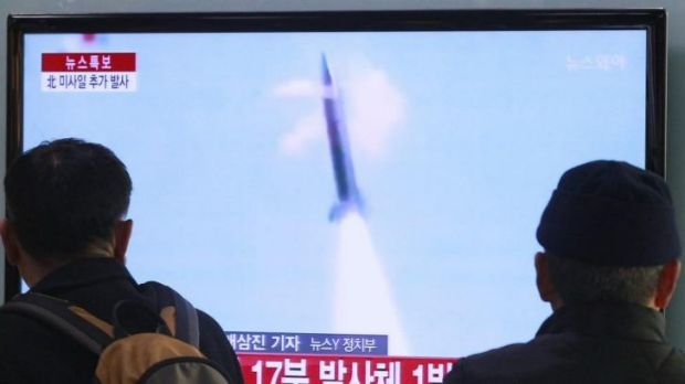 South Koreans watch a TV report on the North's missile test at a Seoul railway station.