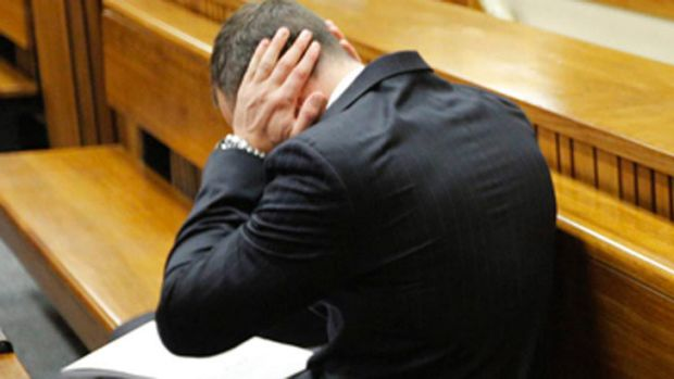 Too much: Oscar Pistorius covers his ears as graphic details of his girlfriend's death are read out in court.