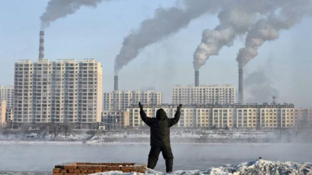 Big issue: A man exercises in the morning as he faces chimneys emitting smoke across the Songhua river in Jilin, ...