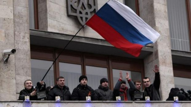 Pro-Moscow demonstrators fly a Russian flag from the balcony of the regional administrative building in Donetsk in ...