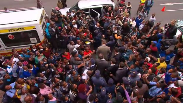 Crowds swarm Oscar Pistorius as he leaves court.