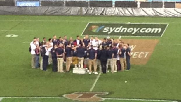 Huddle heroes ... Sydney Roosters players and staff at ANZ Stadium after the grand final win in 2013.