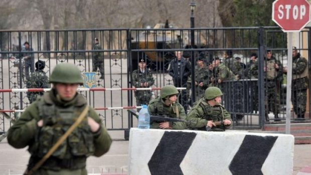 Uneasy neighbours: Members of the Russian armed forces (foreground) stand guard at the gate of a Ukrainian base in the ...