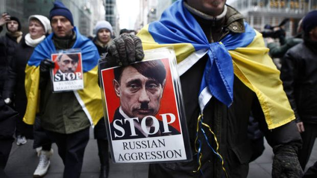 A man holds a sign in a protest against Russian military intervention in the Crimea region of Ukraine  in New York City.
