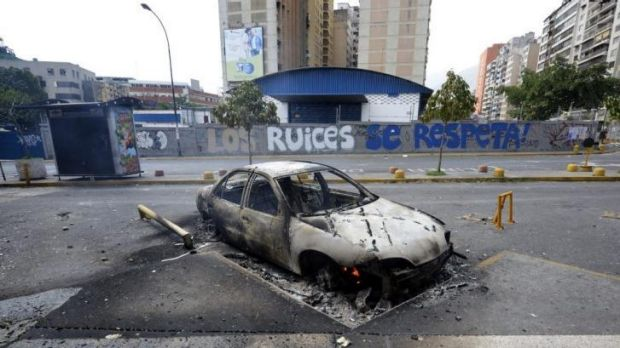 View of a car burnt during an opposition protest against the government of President Nicolas Maduro, in Caracas.
