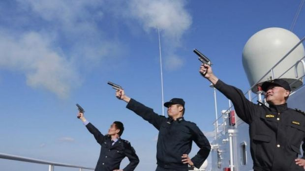 Chinese personnel fire their pistols to signal the start of a naval exercise as they stand on a vessel on the East China Sea.