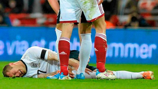 Second best: England midfielder Jack Wilshere lies on the ground after taking a knock in a challenge with Denmark ...