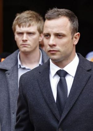 Emotional week ... Oscar Pistorius, right, leaves the high court after the fifth day of his murder trial in Pretoria, ...