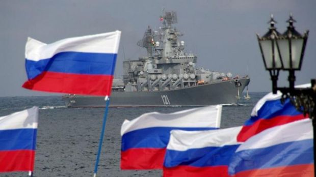 Pro-Russian supporters wave Russian flags to welcome the Russian Black Sea Fleet flagship, the missile cruiser Moskva, ...