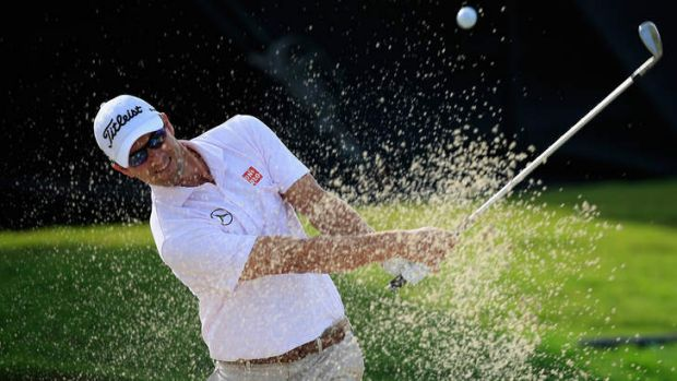 Adam Scott of Australia hits a bunker shot on the 11th hole during the weather-delayed first round of the World Golf ...