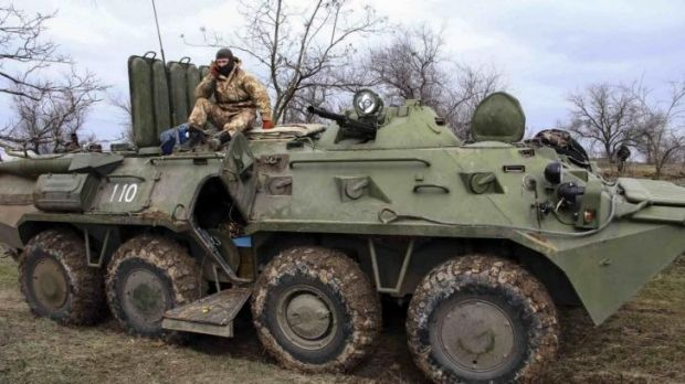 A Ukrainian soldier sits on a military vehicle at a checkpoint at the road near a Crimea region border.