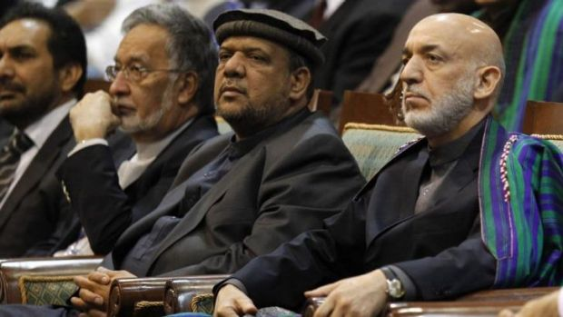 Power broker: Mohammed Qasim Fahim (centre) with Afghan President Hamid Karzai (right) in November 2013.