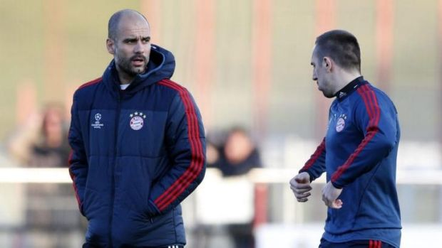 Bayern head coach Pep Guardiola talks to Franck Ribery during a training session in Munich.