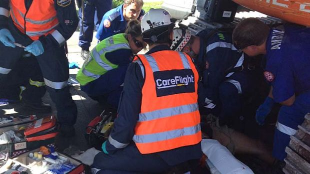Paramedics tend to the man who was caught in an excavator.