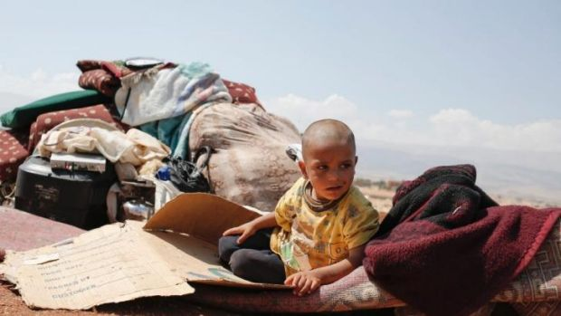 No place to hide: Youssef Akkash, 3, from Aleppo sits among his family's belongings in a makeshift refugee settlement in ...
