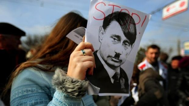 A protester with a caricature of Russian President Vladimir Putin at a pro-Ukrainian rally in the Crimean city of Simferopol.