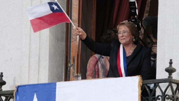 Chile's new President Michelle Bachelet waves a Chilean flag from a balcony at La Moneda presidential palace in ...