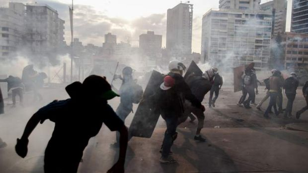 Demonstrators take cover from teargas fired by the police during clashes in Caracas on March 10.