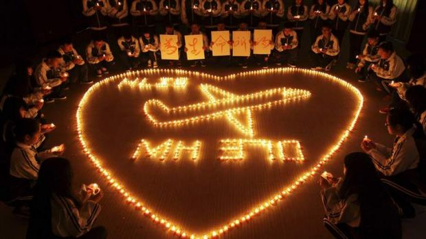 Heartbreak: International school students light candles  for passengers aboard Malaysia Airlines flight MH370, in Zhuji, ...