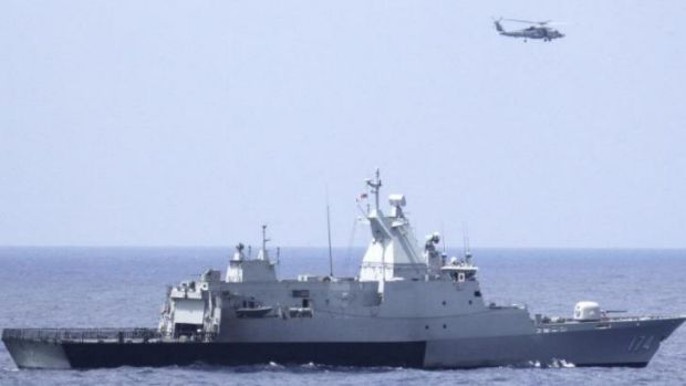 The Royal Malaysian Navy corvette KD Terengganu and a US helicopter conduct a coordinated air and sea search for a ...