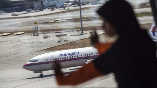 A young girl looks on as a Malaysian Airline aircraft taxis on the tarmac at Kuala Lumpur International Airport.