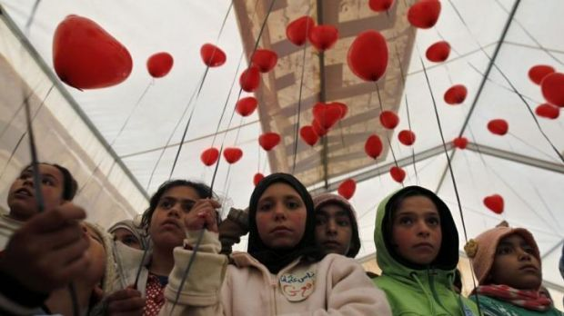 Syrian refugees with red balloons to mark the conflict's third anniversary at the Zaatari refugee camp in Jordan.