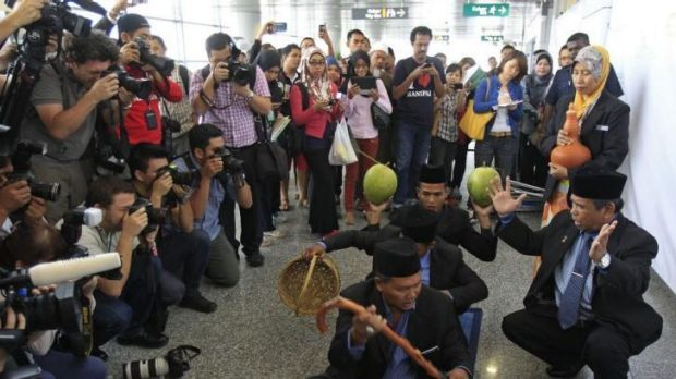 Ibrahim Mat Zin, bottom right, performs a ritual that he says will help rescuers find the plane.