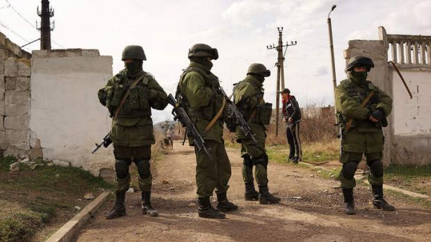 Russian troops stand guard outside a Ukrainian military base.