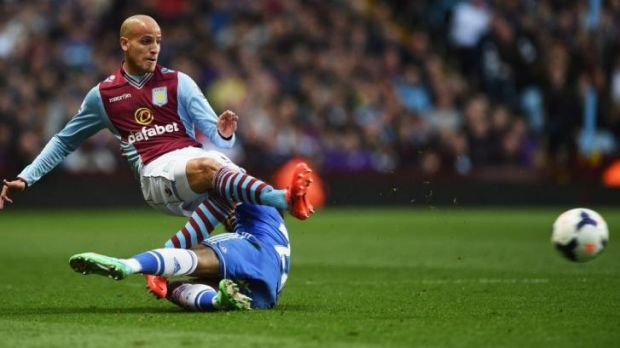 Willian (bottom) of Chelsea receives the first of his two yellow cards for this foul on Karim El Ahmadi of Aston Villa. ...