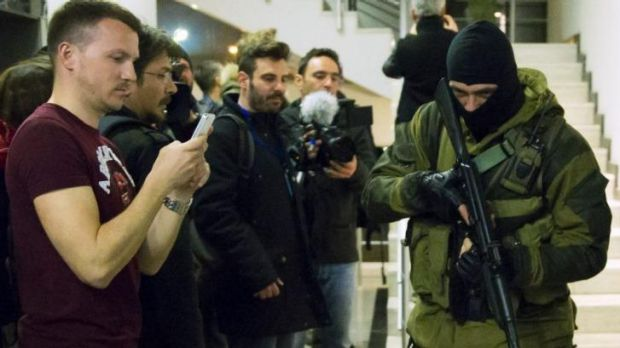 Journalists and guests take a picture of an armed man at the Moscow Hotel in Simferopol.