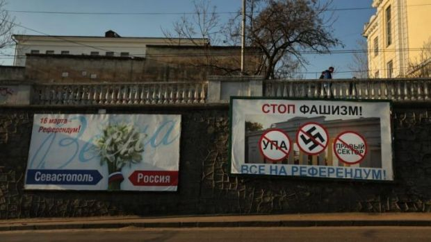 "A billboard in Sevastopol featuring the swastika reads "" Stop Fascism, everyone go to the referendum""."
