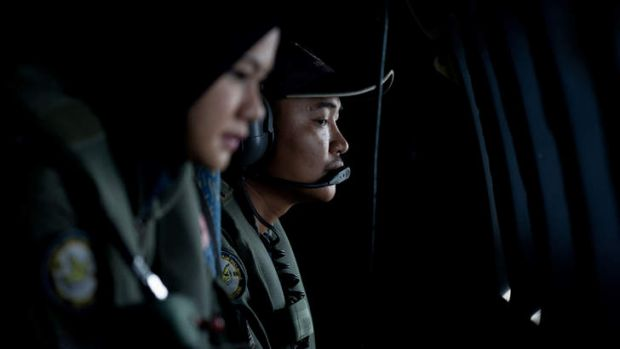 Crew members looking outside windows from a Malaysian Air Force CN235 aircraft working during a search and rescue ...