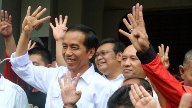 Joko Widodo holds up four fingers to depict his party's position on the ballot paper.