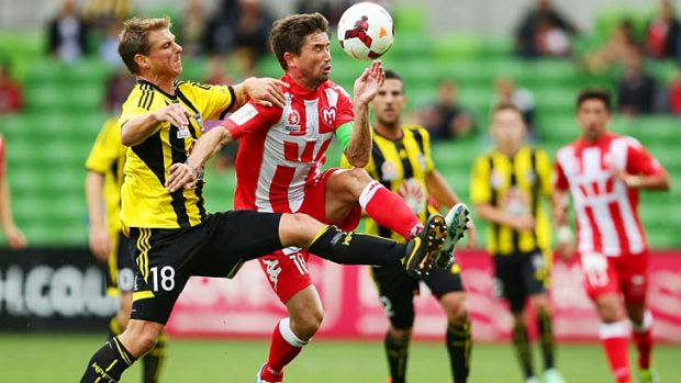 Reckless: Wellington Phoenix defender Ben Sigmund (left) earned his second yellow card after this tackle on Heart's ...