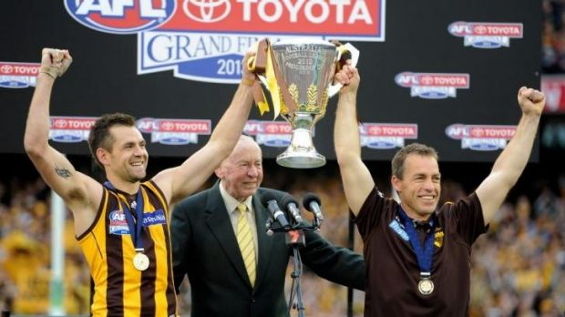 The 2013 premiership coach, at right, with club legend John Kennedy and Hawks captain Luke Hodge.