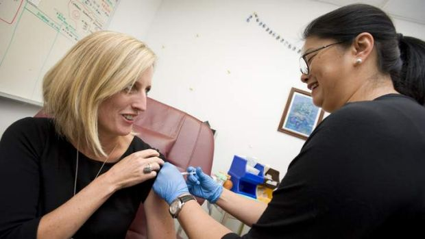 ACT Chief Minister and Minister for Health, Katy Gallagher, receives her flu vaccination from clinical nurse Joyce Ho-Chinn.