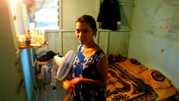 A captive sex worker in the room where she lives and works on the Indonesian island of Batam.