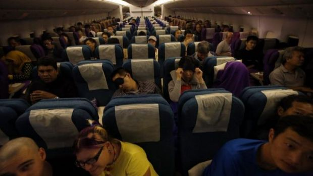Flights continue: Passengers remain in their seats on board Malaysia Airlines Boeing 777-200ER flight MH318 as it ...