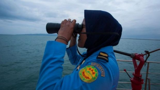 A member of Indonesia's National Search and Rescue looks for missing Malaysian Airlines flight MH370 in the Andaman Sea ...